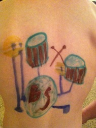 A drum-set on Bean's back. The BS stands for Black Sabbath.